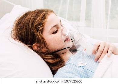 Cute little girl oxygen mask on her face on bed in the hospital