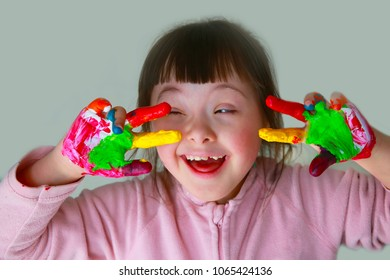 Cute little girl with painted hand. Isolated on grey background.