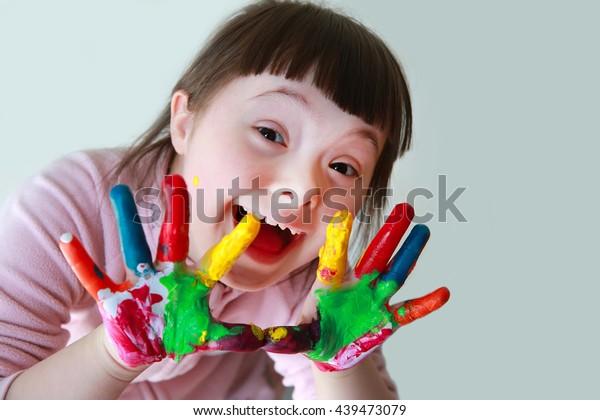 Kleines, niedliches Mädchen mit lackierten Händen. Einzeln auf grauem Hintergrund.