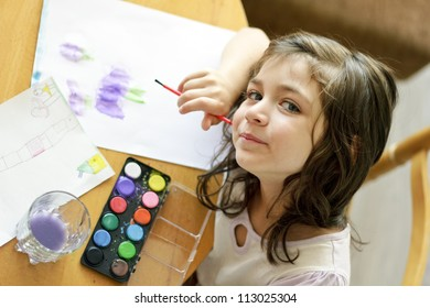Cute little girl painting with brush in preschool. Child care.