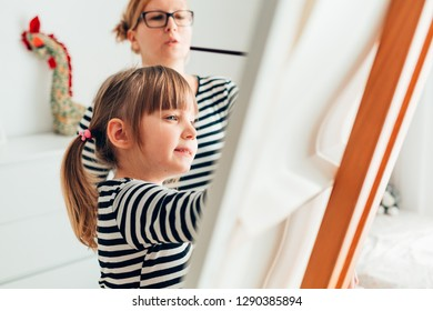Cute little girl painting with her mother using easel stand at home