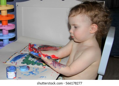 Cute little girl painting on her body with finger paints