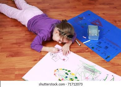 Cute little girl painting on the floor
