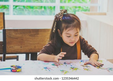 Cute little girl painting a picture by her hand at the school  or kindergarten. Concept for art and creative education. Kids hobby.