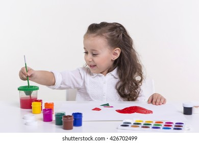 Cute little girl painting picture on a light background