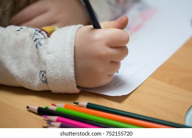 Cute little girl paints and tinkers with colored pencils and scissors