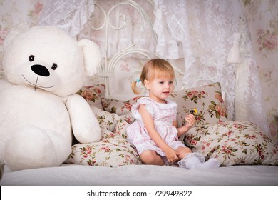 Cute little girl in pajama hugging her toy hare on the bed at home, happy childhood concept, indoor horizontal portrait