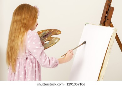 Cute little girl with a palette and brush near the easel. At the easel a blank white sheet of paper on which you can draw a picture or apply any advertising inscription. The concept of art, children's