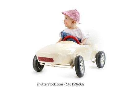 cute little girl in pedal car isolated on white