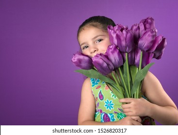 Cute little girl peeking from behind bouquet of  tulips isolated on purple background