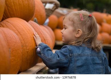Cute little girl picking halloween pumpkin at farmer's market