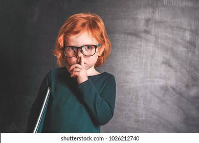 Cute little girl picking her nose on blackboard background. Bad habits. Finger in nose. Kid wearing glasses with school bag and book.