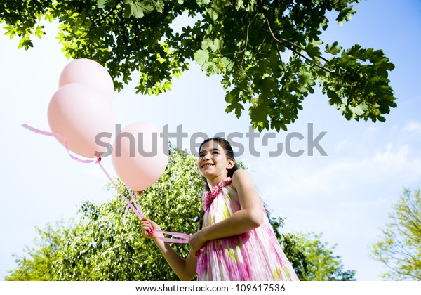 Cute little girl with pink balllons outdoors, low angle view