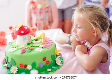 Cute little girl in a pink dress is making a wish before blowing the candles on her fairy garden birthday cake