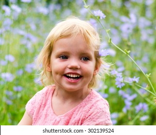 Cute little girl in a pink dress smiling in park.