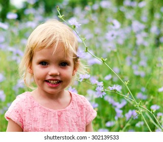 Cute little girl in a pink dress smiling in park looks at camera.