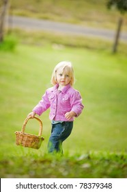 A cute little girl in a pink jacket is holding a basket at the top of a hill.