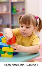 Cute little girl play with building bricks in preschool