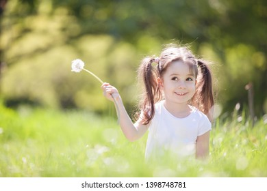 Cute little girl play in the park. Beauty nature scene with colorful background at summer or spring season. Family outdoor lifestyle. Happy girl relax on green grass