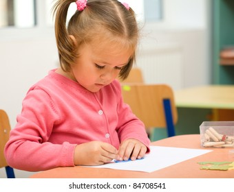 Cute little girl is play with pencils in preschool
