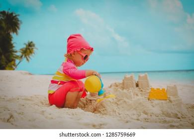 cute little girl play with sand on beach