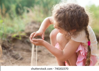 Cute Little girl play with sand in park on a summer day at sunset.