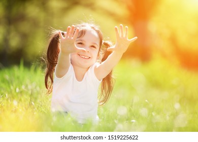 Cute little girl play in the sunny park. Beauty nature scene with colorful background at summer or spring season. Family outdoor lifestyle. Happy girl relax on green grass