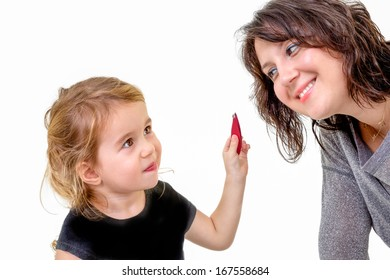 Cute little girl with a playful expression wanting to apply her mothers makeup holding it up in her hand as her mother bends forwards to oblige with a smile, isolated on white