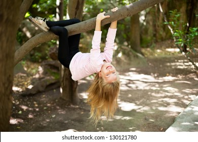 Cute little girl playfully hangs from a tree limb