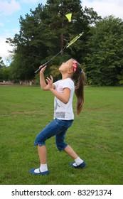 Cute little girl playing badminton on green grass outdoor.