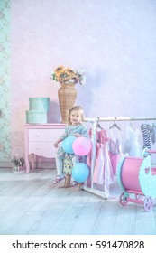 Cute little girl playing with balloons in a beautiful nursery.