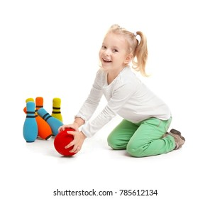 Cute little girl playing bowling on white background