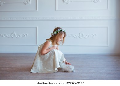 Cute little girl playing with bunny. Spring and easter portrait of beautiful child with rabbit.