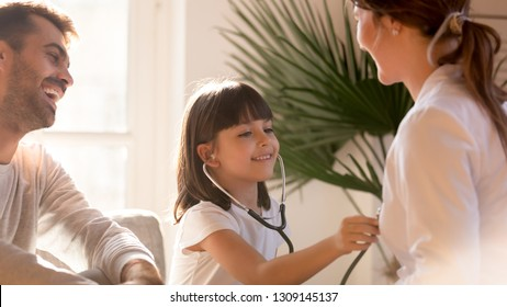 Cute little girl playing as doctor visiting pediatrician while doctor and dad laughing, playful funny happy child holding stethoscope pretending nurse checking gp in hospital, fun children healthcare