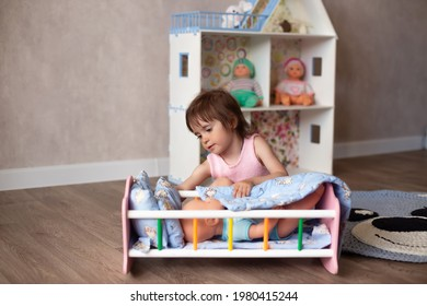 Cute little girl is playing with a doll at home. The child puts the doll to sleep in a toy bed. Role-playing games for children