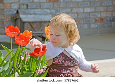 Cute Little Girl Playing with Flowers