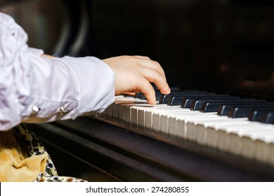 Cute little girl playing grand piano in music school, childhood concept