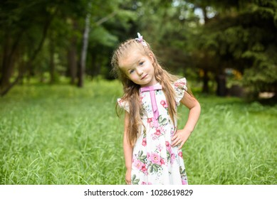 Cute little girl is playing in green nature Outdoor. Happy and Healthy Smiling little child Girl with healthy smile relaxing in the Summer Park