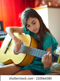 Cute little girl playing guitar indoor in her bedroom