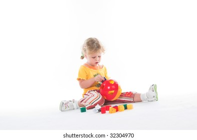 Cute little girl playing with her toys in the studio