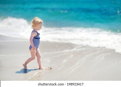 Cute little girl playing jumping over the waves