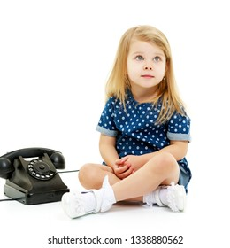Cute little girl playing with an old phone. Concept retro, nostalgia. Isolated on white background.