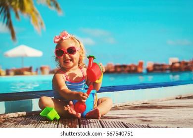cute little girl playing on tropical beach