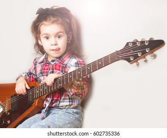 Cute little girl playing on electric guitar. Rock and alternative