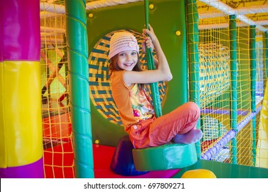 Cute little girl is playing on the playground. The girl is riding on a swing.