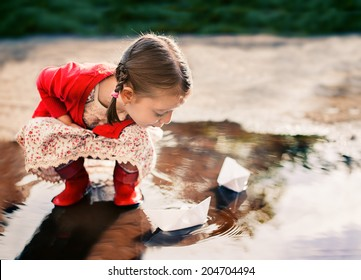 cute little girl playing with paper boat