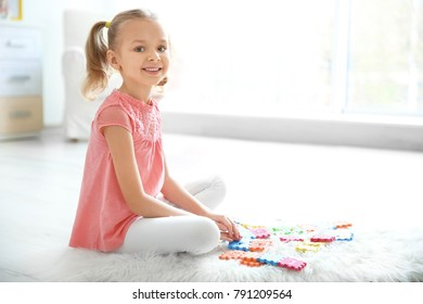 Cute little girl playing with pazzles at home