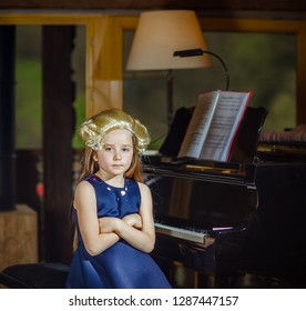 Cute little girl playing piano, dressing in retro Mozart periwig, indoor