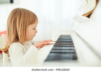 Cute little girl playing piano in a light room.