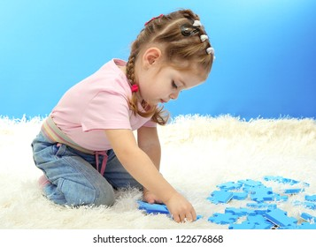 cute little girl playing with puzzles, on blue background